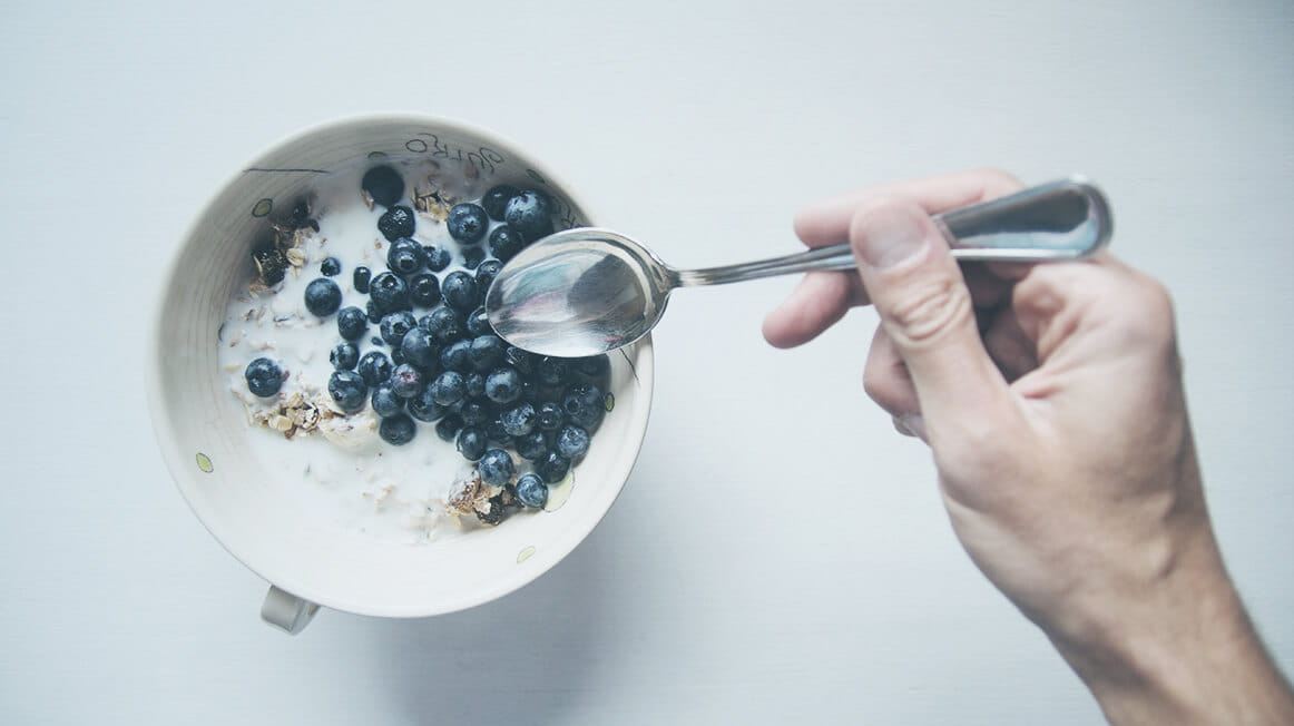 bowl of cereal with milk, fruit, spoon