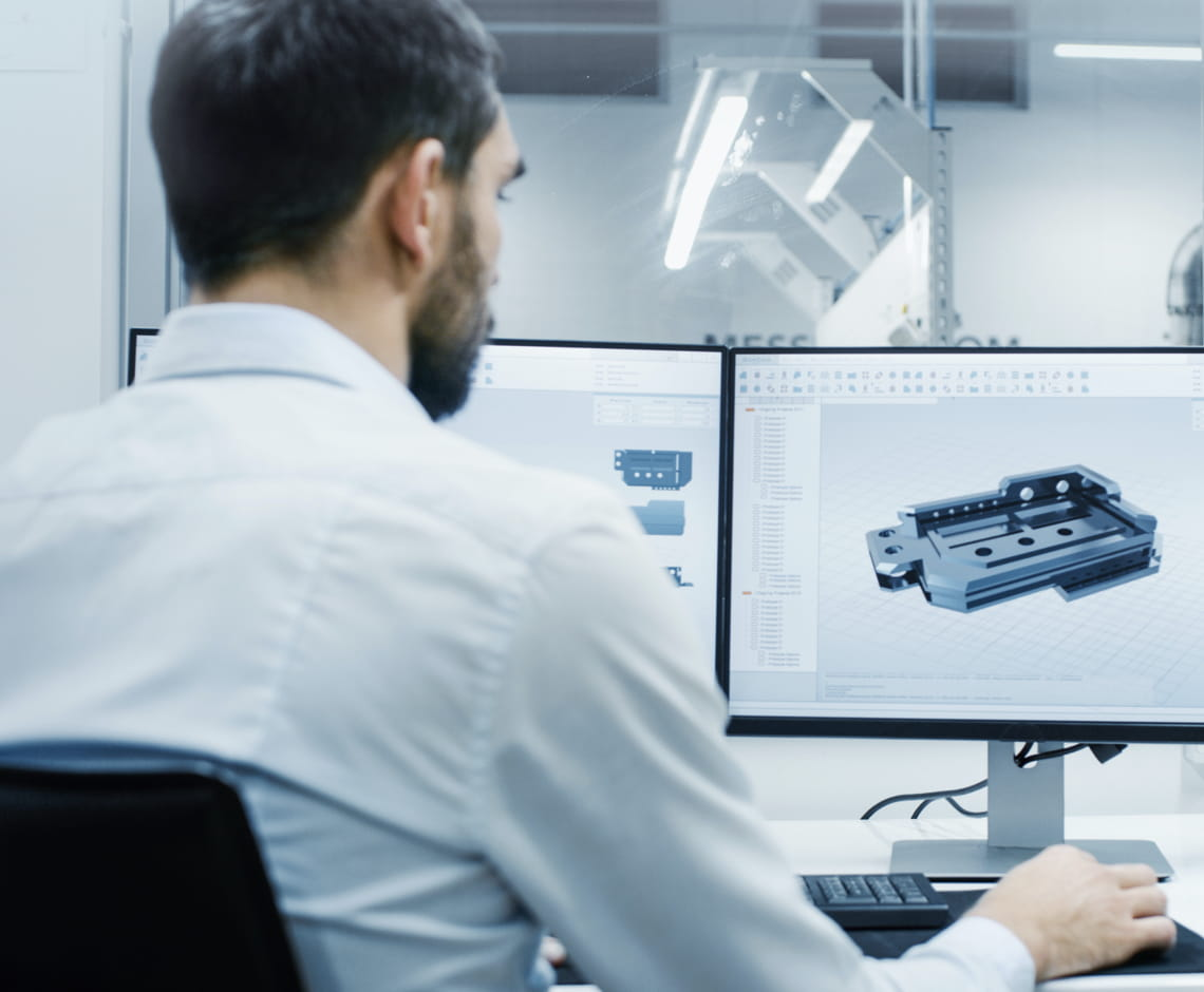 office worker on computer looking at CAD drawing