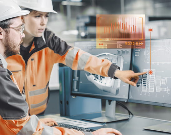 two workers in hard hats pointing to computer screen