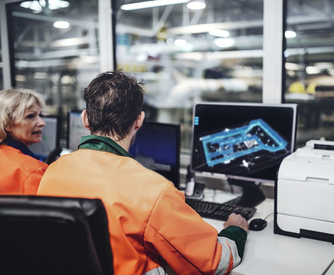 workers overlooking plant at computers